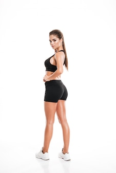 Full length of attractive fitness woman standing and looking back
