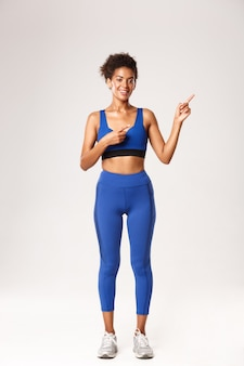 Full length of attractive smiling african-american woman with combed hair, wearing blue sportswear