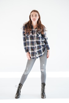 Full length of attractive woman in plaid shirt and jeans