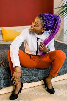Full length of attractive woman with blue hair in stylish clothing. african female fashion model