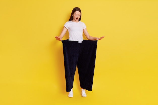 Full length attractive young female shows her old huge pair of pants, looks shocked and surprised, looking down with opened mouth, lady after weight loss posing isolated on yellow wall