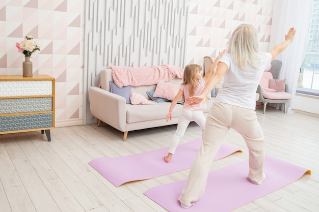 Full length back side view smiling blond mother on yoga mat with cute playful little preschool daughter do various exercises.