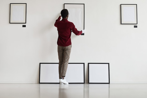 Full length back view at african-american man hanging blank frames on wall while planning art gallery or exhibition,