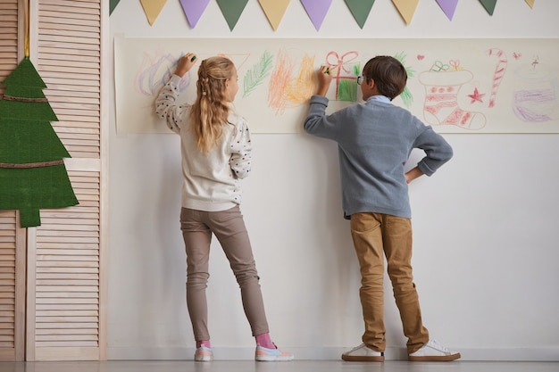 Full length back view at boy and girl drawing on walls while enjoying art class in school, copy space