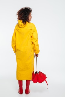 Full length back view image of african woman in raincoat
