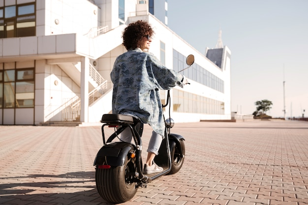 Full-length back view image of young woman rides on motorbike
