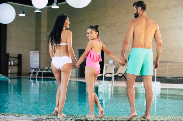 Full-length back view photo of young excited and happy family while they go in pool in resort spa centre. vacation in a summer hotel