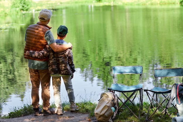Full length back view portrait of father and son standing by lake and enjoying nature during hiking or fishing trip, copy space