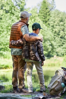 Full length back view portrait of father and son standing by lake and enjoying nature during hiking or fishing trip
