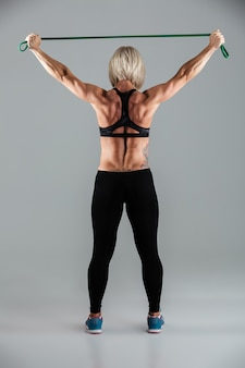 Full length back view portrait of a muscular adult sportswoman