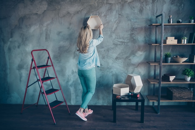 Full length back view portrait of woman hanging shelf on gray wall