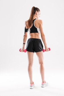 Full length back view portrait of a young fitness woman