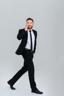 Full length bearded business man in black suit moves with hand in pocket and talking at phone isolated gray background