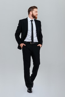 Full length bearded business man in black suit with hands in pockets looking aside in studio isolated gray background