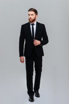 Full length bearded business man holding to suit in studio and looking aside isolated gray background