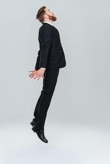 Полнометражный бородатый деловой человек в черном костюме, летевшем в студии. вид сбоку. изолированный серый фон