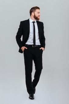 스튜디오에서 격리된 회색 배경을 옆으로 바라보는 주머니에 손을 얹고 검은 양복을 입은 수염 난 사업가