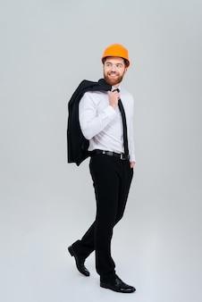 Full length bearded engineer standing sideways in orange helmet with jacket on shoulder.