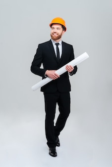 Full length bearded engineer in suit and helmet holding twisted layout in hands and looking aside