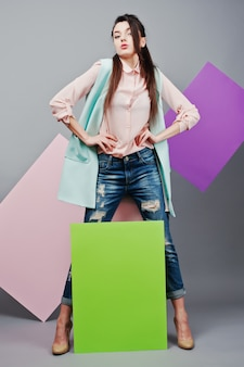 Full length of beautiful girl, with green blank advertising board , over gray background and pink and violet banner