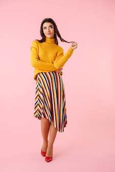 Full length of a beautiful pensive young woman wearing colorful clothes standing isolated over pink