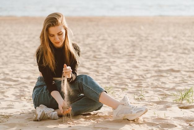 完全な長さの美しい女性の夕暮れ時のビーチに座って砂を注ぐ。スローライフ
