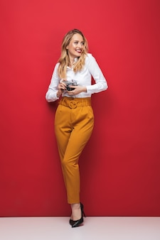 Full length of a beautiful young blonde woman standing over red background, holding photo camera
