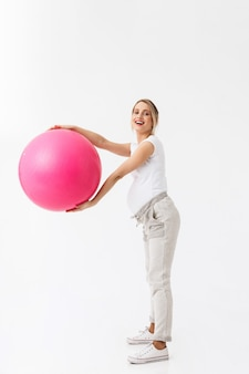 Full length of a beautiful young pregnant woman doing sport exercises with fitness ball isolated over white background