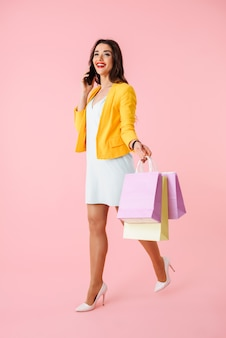Full length of a beautiful young woman wearing colorful clothes standing isolated over pink, carrying shopping bags, holding mobile phone