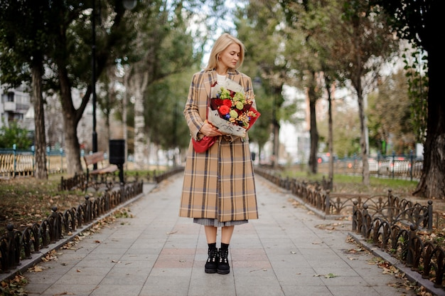Full-length blonde woman in plaid coat holding a bright bouquet of flowers standing on alley