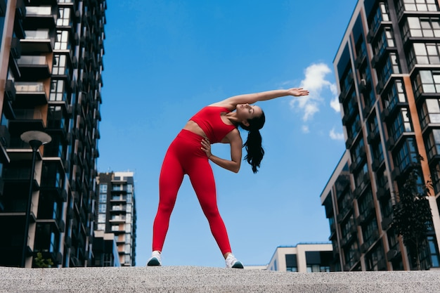 脇に傾いて運動をしている愛らしい柔軟な若い女性の全身