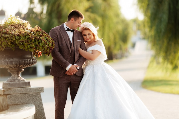 Full length body portrait of young bride and groom running on green grass of golf course. happy wedding couple walking through golf course, copy space