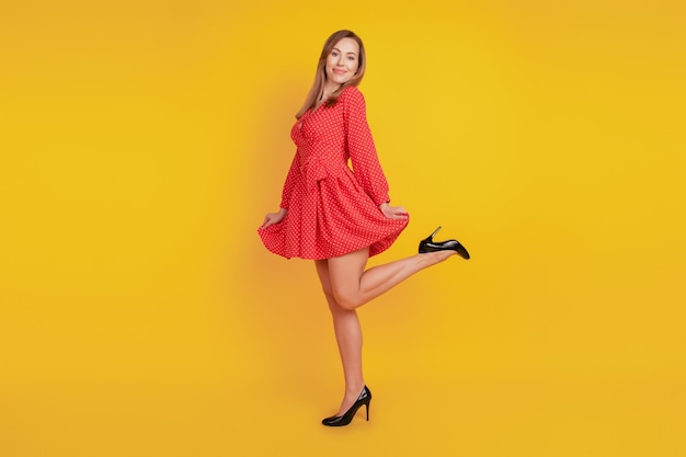 Full length body size of carefree funky girl dance hold red mini skirt have fun on yellow wall