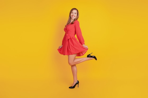 Full length body size of cheerful funny girl dance hold red mini skirt have fun on yellow wall