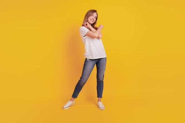 Полная длина тела позитивной радостной девушки танцует беззаботно, развлекается на желтом фоне