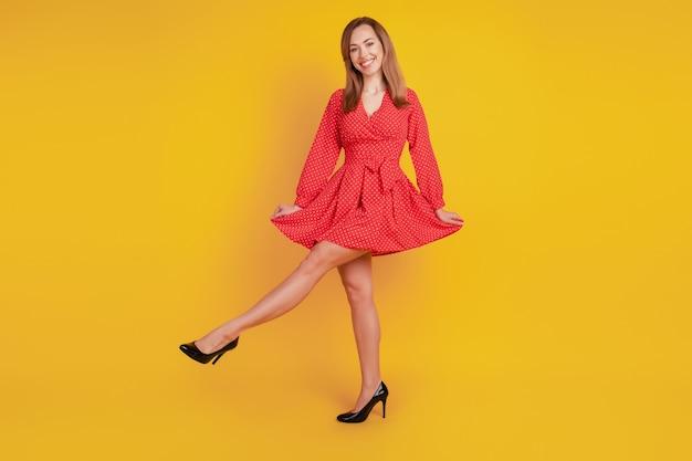 노란색 배경에 긍정적인 기쁜 소녀 춤의 전체 길이 몸 크기는 빨간색 멋진 드레스를 입고