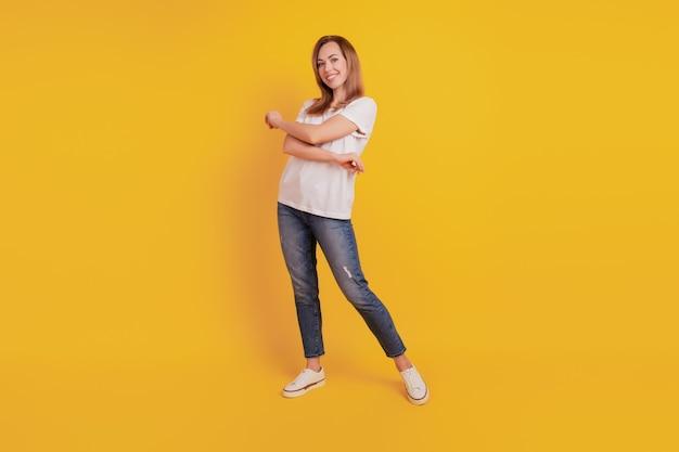 노란 벽에 긍정적인 기쁜 소녀 댄스의 전체 길이 몸 크기
