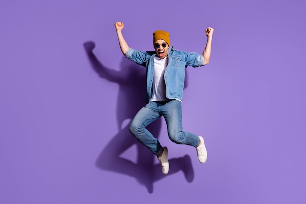 Full length body size photo of cheerful crazy positive strong screaming shouting man with ecstatic facial expression isolated over purple vivid color background