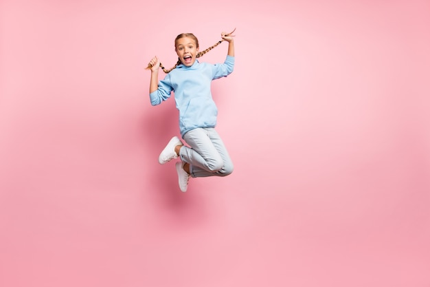 Full length body size photo of cheerful positive ecstatic overjoyed rejoicing girl jumping up wearing jeans denim blue sweatshirt sweater isolated over pastel color background