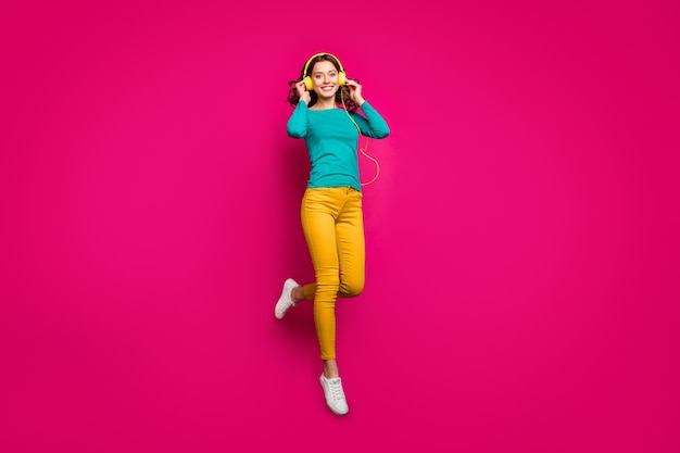 Full length body size photo of cheerful positive nice pretty cute charming girlfriend wearing yellow pants trousers white footwear smiling toothily isolated jumping over vivid pink color background