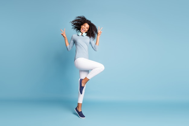 Full length body size photo of cheerful positive nice pretty youngster jumping dancing showing you v-sign in footwear white pants isolated pastel blue color background