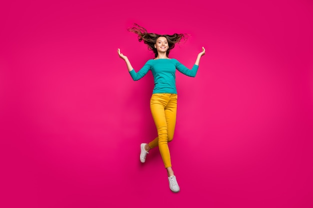 Full length body size photo of cheerful positive running girlfriend jumping throwing her hair up smiling toothily in teal shirt isolated fuchsia vivid color background