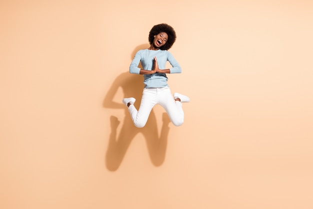 Full length body size photo of curly funny girl with dark skin jumping keeping hands together begging asking isolated on beige color background