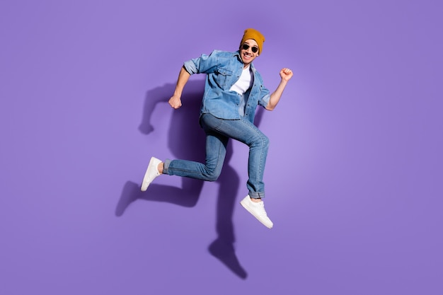 Full length body size photo of ecstatic rejoicing overjoyed guy enjoying sport running trying to reach sales isolated over vivid purple color background