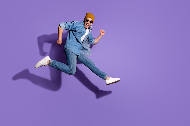 Full length body size photo of excited cheerful ecstatic handsome surprised amazed astonished guy sportive running towards discounted store isolated over vivid color purple background