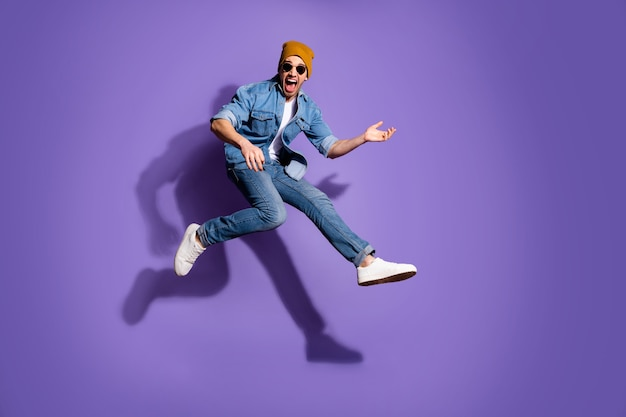 Full length body size photo of excited guitarist jumping up running fast playing guitar wearing jeans denim trendy stylish isolated over purple vibrant color background