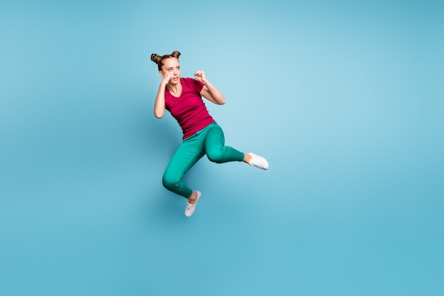 Full length body size photo of focused concentrated girl readying to fight empty space nearby wearing green pants trousers footwear isolated over blue pastel color wall