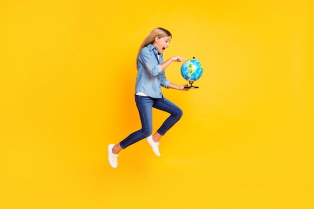 Фотография в полный рост изумленной прыгающей старшеклассницы, держащей земной шар, указывающей на континент, крича изумленно изолированной на ярко-желтом цветном фоне