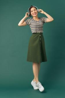 녹색 배경에 격리된 헤드폰으로 노래를 부르며 음악을 듣고 있는 아름다운 소녀의 전신 크기 사진