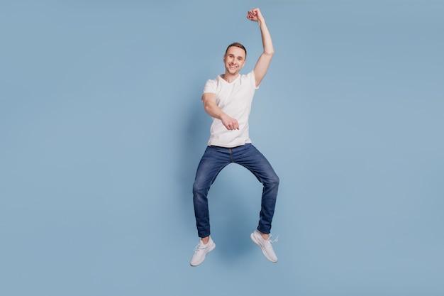 파란색 배경 위에 격리된 밝은 갈색 머리의 매력적인 남자 점프 타기 말의 전체 길이 신체 크기 사진
